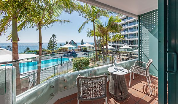Guest balcony overlooking hotel pool with ocean backdrop