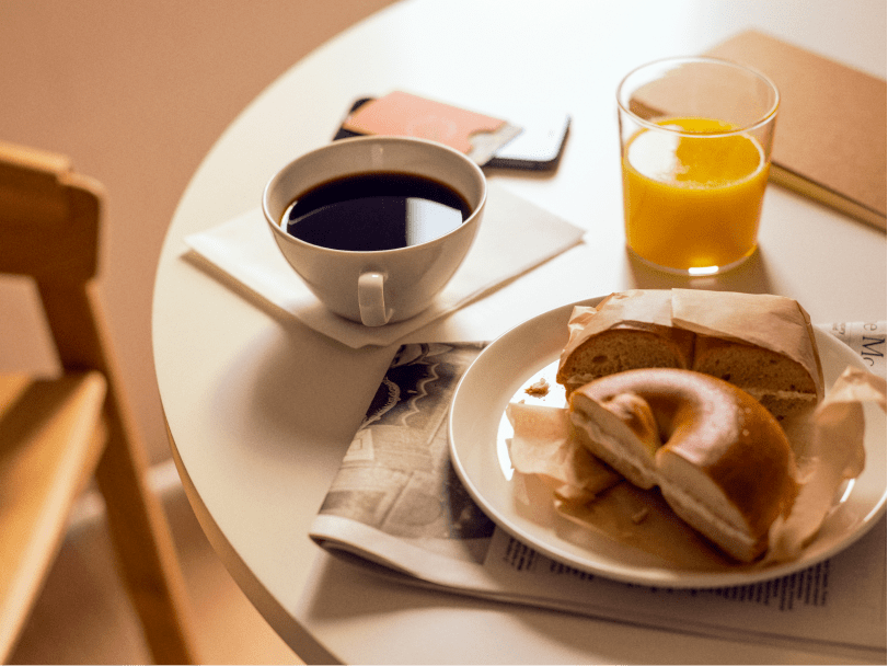 Sunlight hits a round table holding a cup of coffee, orange juice, a bagel and a newspaper.