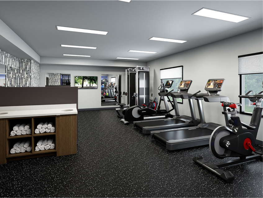 Well-lit fitness studio with towels, treadmills, an exercise bike and other equipment.