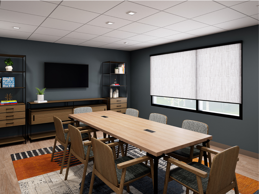 Warm and bright meeting room with a wood conference table, a striped rug, a flat screen monitor mounted to the wall and eight chairs.