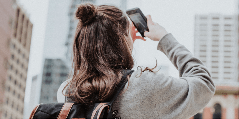 A traveller wearing a cool rucksack lift her phone to take a picture of the city skyline before her.
