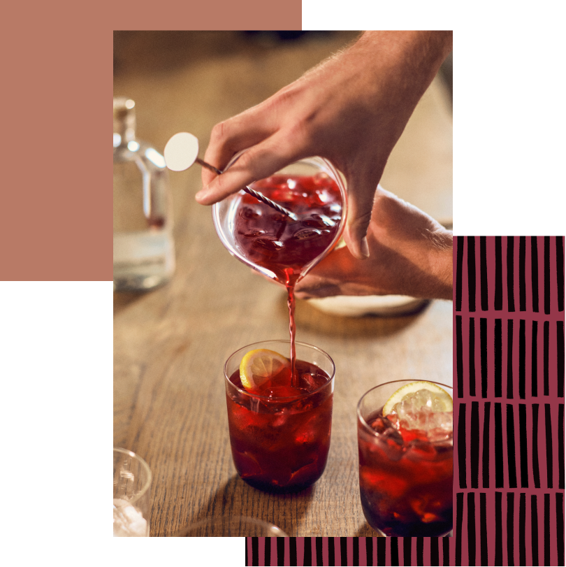Close up of hands pouring a bright red drink into a pair of glasses with bright lemon slices and ice.
