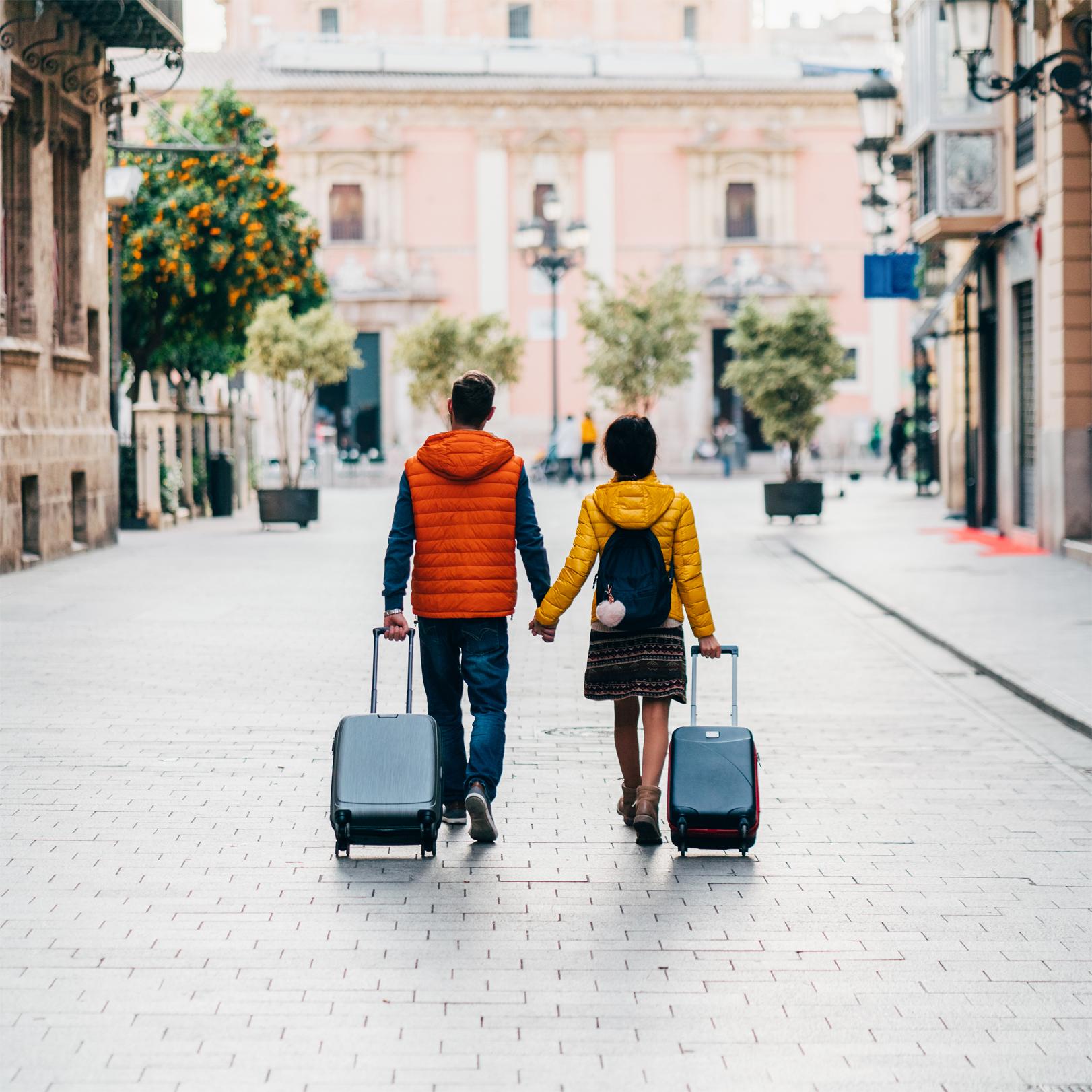 Un hombre y una mujer caminan de la mano por una calle adoquinada mientras jalan de sus maletas con ruedas.