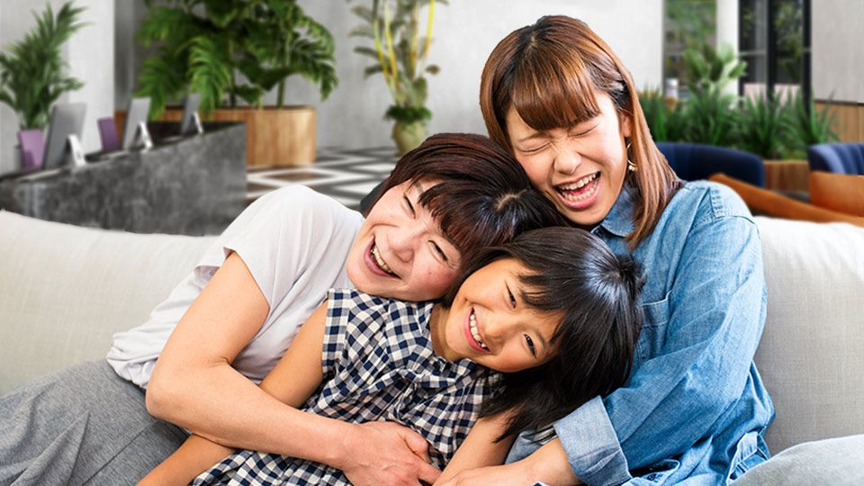Mom and two kids lauhging on couch
