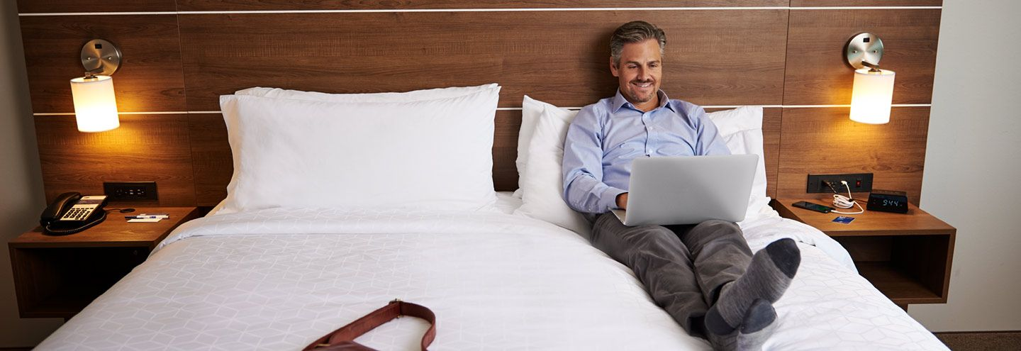 Man on hotel bed using laptop