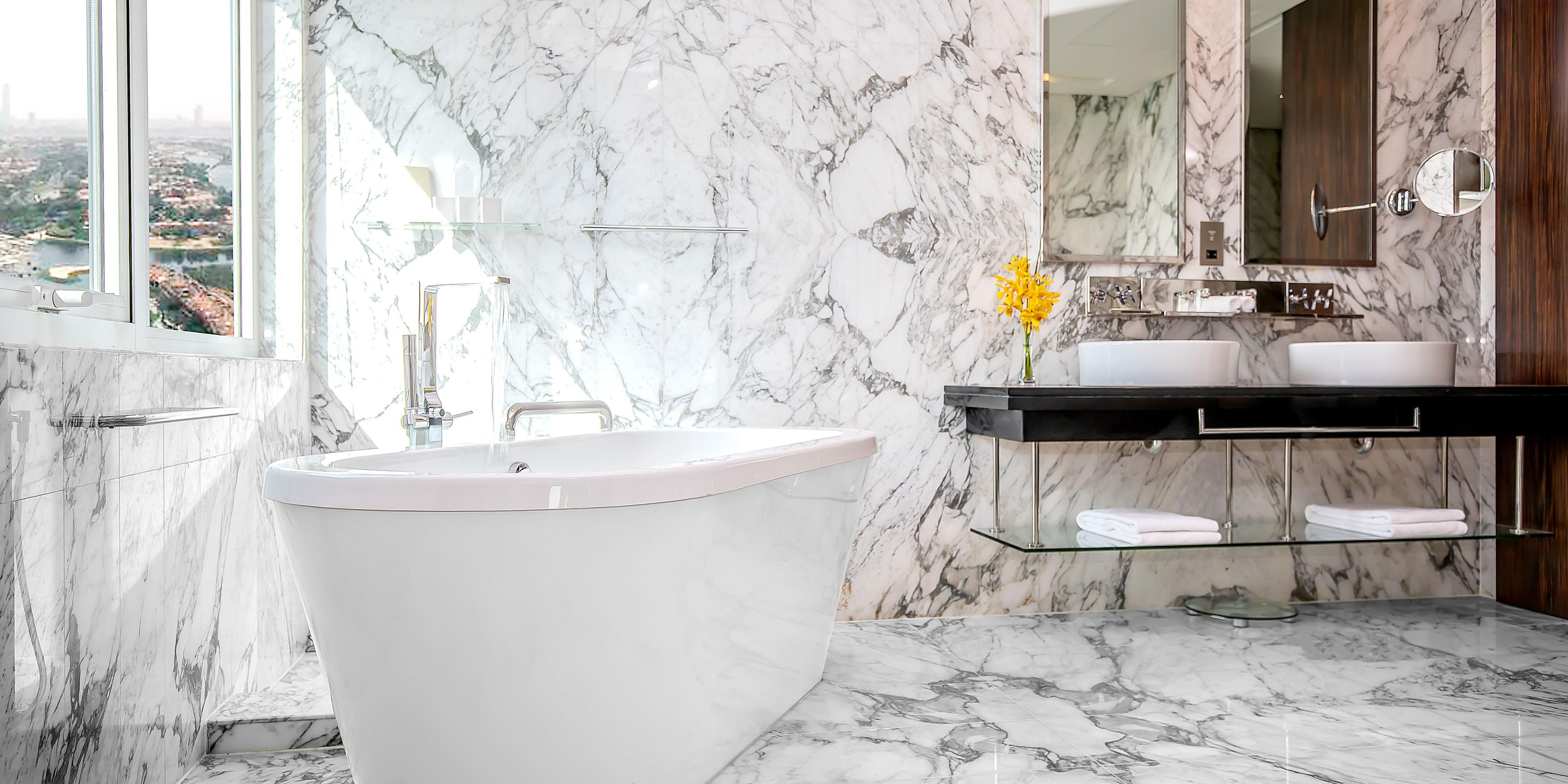 Stand-alone bathtub and double-vanity area of the Deluxe suite